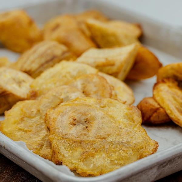 Des morceaux de bananes plantains frites jonchent une plaque à cuisson.