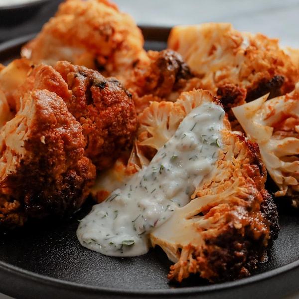 Des morceaux de chou-fleur rôti style buffalo, accompagnés de sauce au fromage bleu.