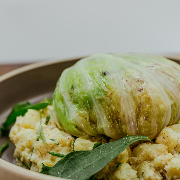 Un plat avec un choux farci, accompagné d'une salade de pommes de terre.
