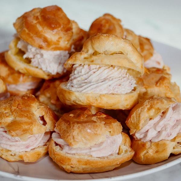 Des gougères à la mousse de jambon dans une assiette blanche.