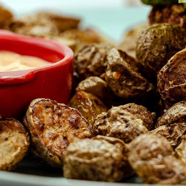 Une assiette de pommes de terre accompagnées d'une sauce.