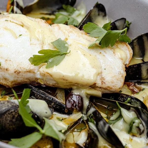 Eau folle de flétan, moules et légumes servie dans un grand bol blanc.