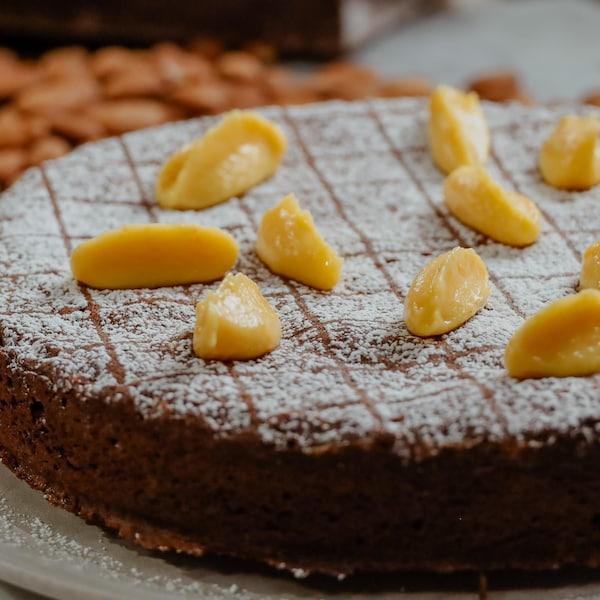 Torta caprese parfumée à l'orange servie sur une assiette.
