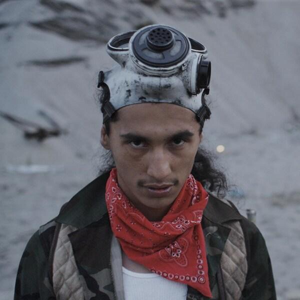 Deux jeunes hommes, en extérieur, avec un masque à gaz sur le front et des armes improvisées.