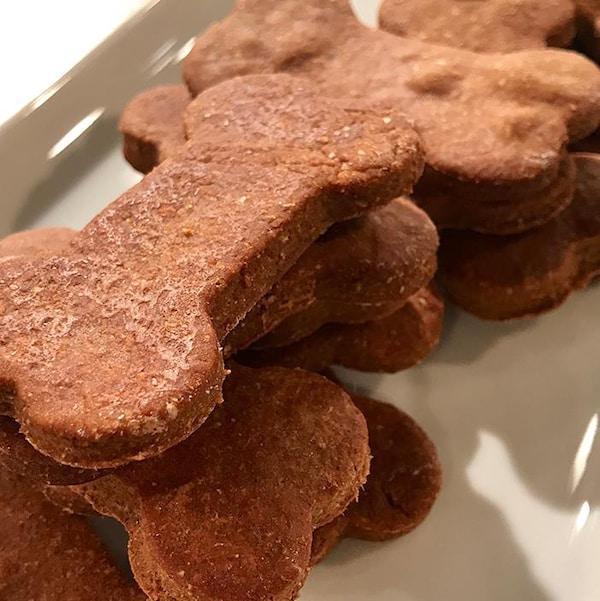 Des biscuits en forme d'os posés dans un plateau de service blanc.
