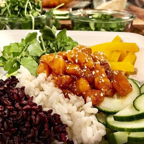 Une assiette de poké composée de riz, de poisson, de betteraves et de concombres.