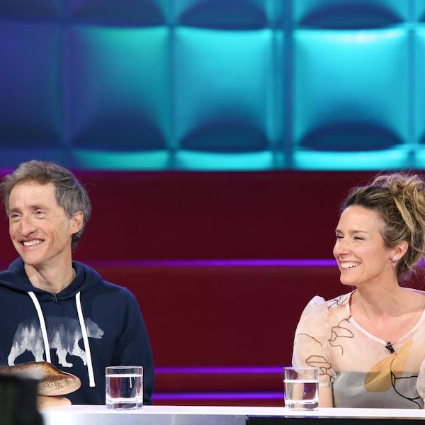 Le couple est assis côte à côte dans un studio de télévision et sourit en regardant l'animateur qu'on ne voit pas.