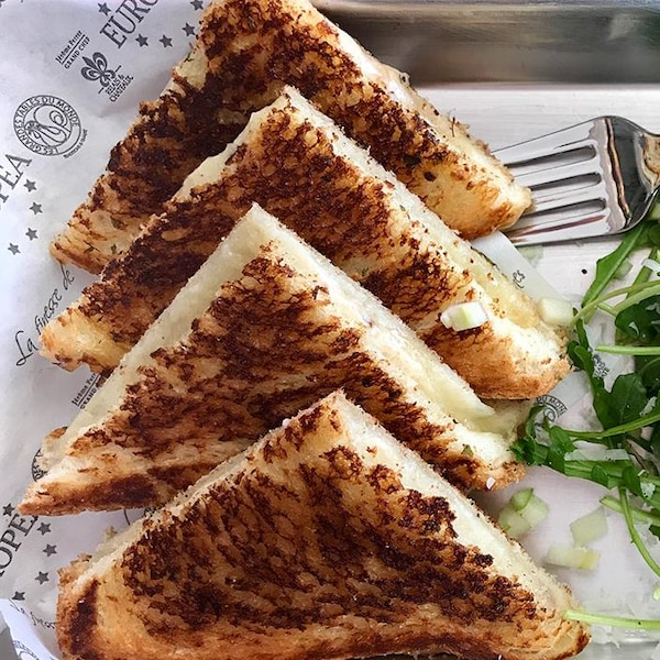 Un grilled cheese accompagné d'une salade.