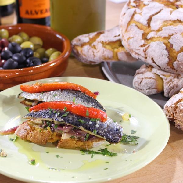Filets de sardines grillés dans une assiette avec la compote d'oignons.
