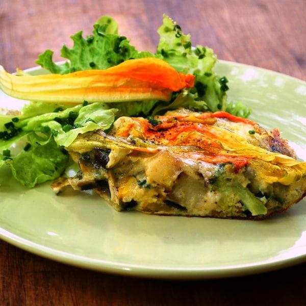 Quiche pas de croûte accompagnée d'une fleur de courgette et d'une salade.