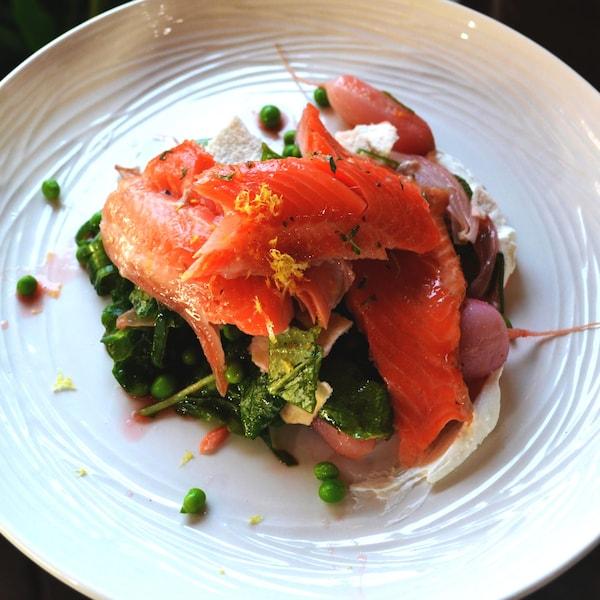 Truite fumée à chaud et salade de radis, de petits pois et d'oignons nouveaux dans une assiette blanche.