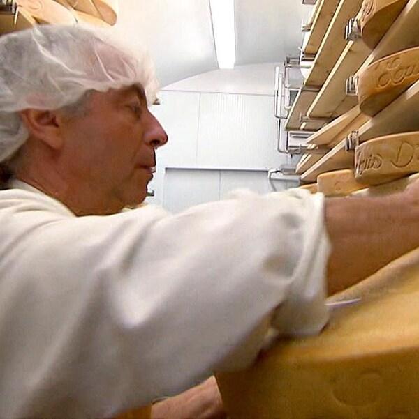 Un fromager qui place des meules de fromage.