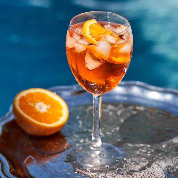 Un verre de spritz aperol sur fond bleu.