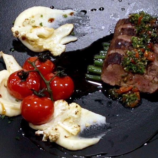 Bœuf grillé, crémeuse de pommes de terre et légumes rôtis dans une assiette noire.