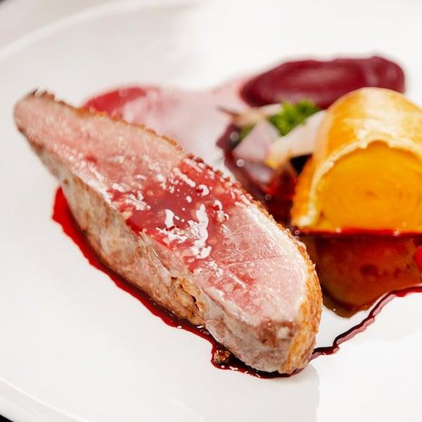 Une assiette avec du magret de canard, purée de betterave, pithiviers de betteraves jaunes et jus tonka.