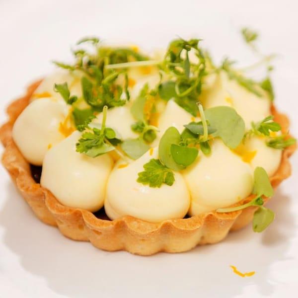 Une tartelette au citron dans une grande assiette blanche.