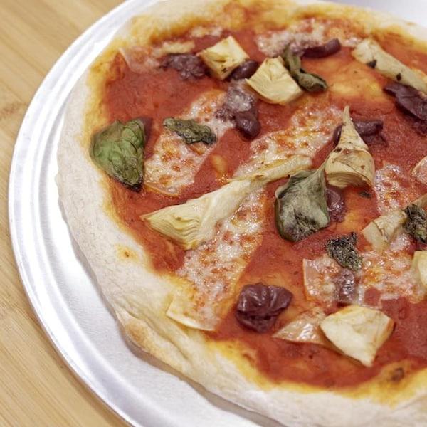 Une grande pizza tomates, olives, artichauts et fromage présentée sur une plaque à pizza.