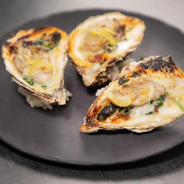 Trois huîtres style Rockefeller aux lardons de sanglier dans une assiette en terre cuite noire.