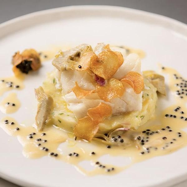 Une grande assiette, avec au centre une morceau de rorue d'Islande cuite au four, brandade de morue salée, artichauts au vin blanc, croustilles de pomme de terre, beurre blanc au caviar.