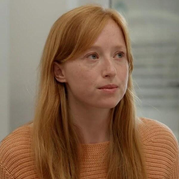 Une jeune femme aux longs cheveux roux.