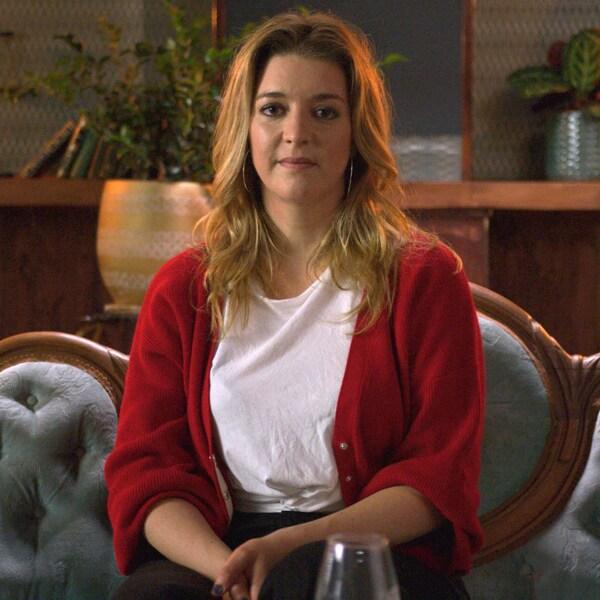 La jeune femme porte un cardigan rouge et est assise dans un canapé vintage.