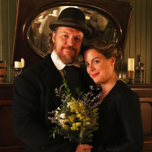 Un couple à la fin du 19e siècle pose avec un bouquet de fleurs.
