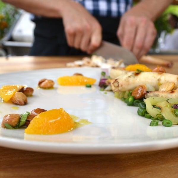 Pieuvre grillée et salade estivale avec des suprêmes d'orange dans une assiette blanche.