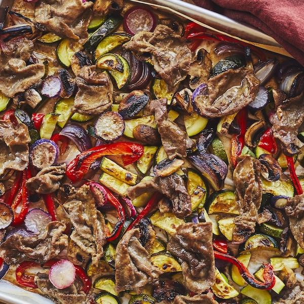 Une plaque remplie de légumes grillés et de tranches minces de bœuf.