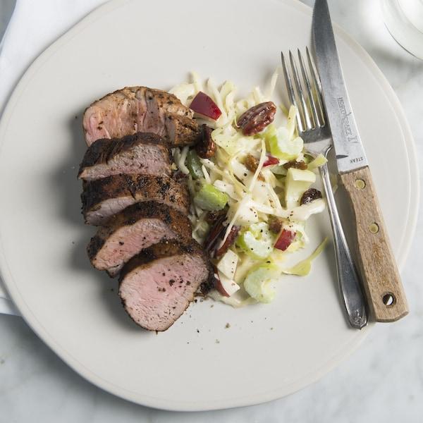 Des tranches de filet de porc sont disposées dans une assiette à côté d'une salade.