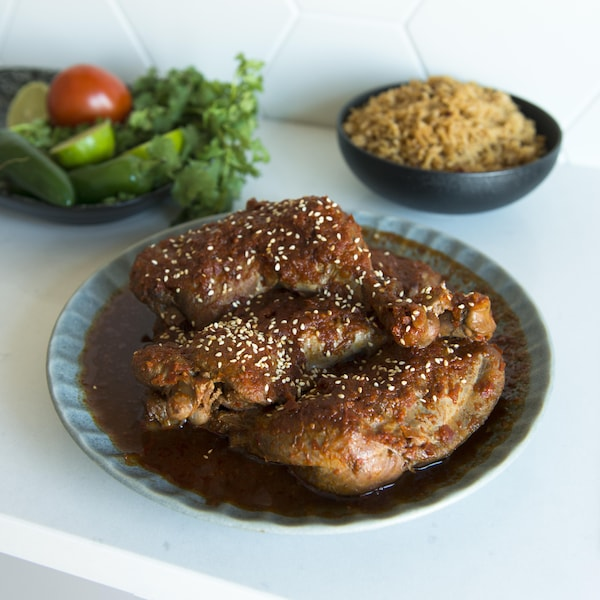 Un bol contient des pièces de poulet dans une sauce tomatée. Sur la table il y a aussi un bol de salade et un bol de riz.