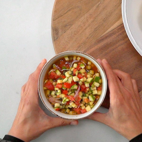 Un bol rempli de salsa fraîche qu'on s'apprête à verser sur un poisson.