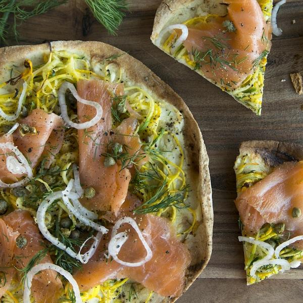 Une pizza avec des oignons, des câpres et de l'aneth.