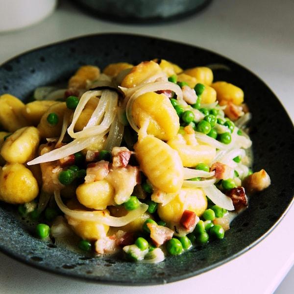 Un bol de gnocchis avec des oignons, des lardons, des pois.