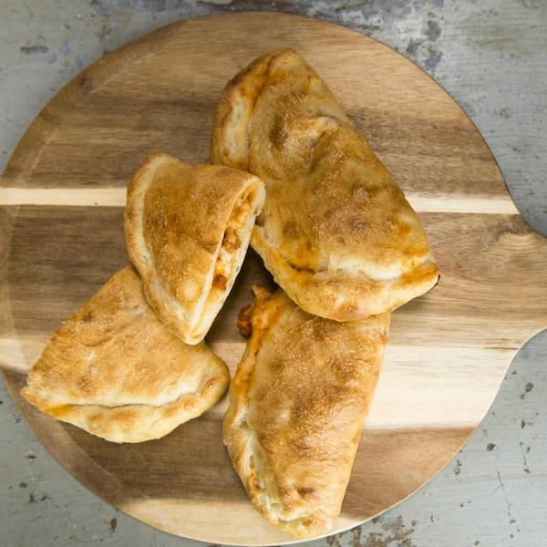 Des petites pizzas disposées sur une planche de bois.