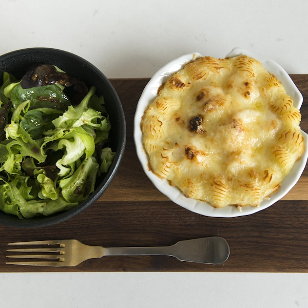 Un bol de salade est à côté d'un plat de coquille Saint-Jacques.