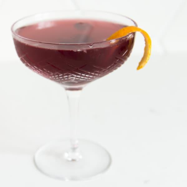 Une coupe est servie avec un zeste d'orange.