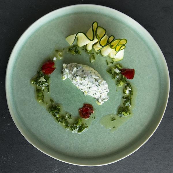 Une assiette avec du fromage crémeux, de l'huile, du pesto et des tranches de zucchinis.