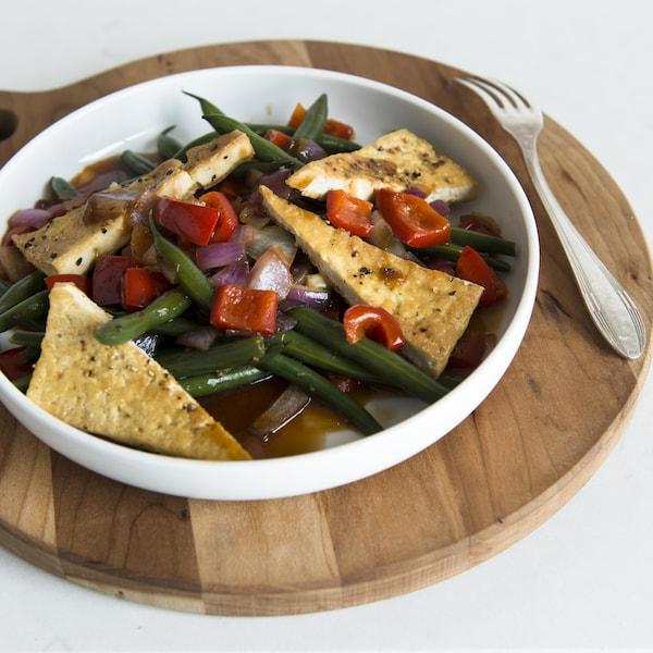 Le plat est dans une assiette creuse sur une planche de bois ronde.