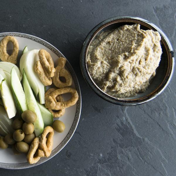 Un bol de trempette est accompagné de crudités, d'olives et de pains bâtons.