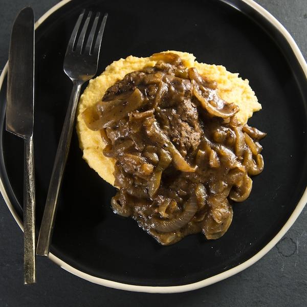 Le plat dans dans une assiette sur un comptoir de pierre.