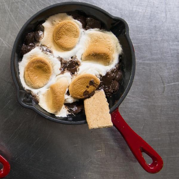 Deux casseroles en fonte contiennent la trempette de chocolat fondu et de guimauve.