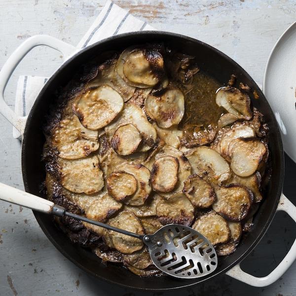 Le plat est dans une casserole sur la la table à côté d'une assiette.
