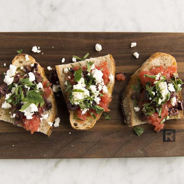 Trois morceaux de pain garnis de salade de tomates sont sur une planche de bois.