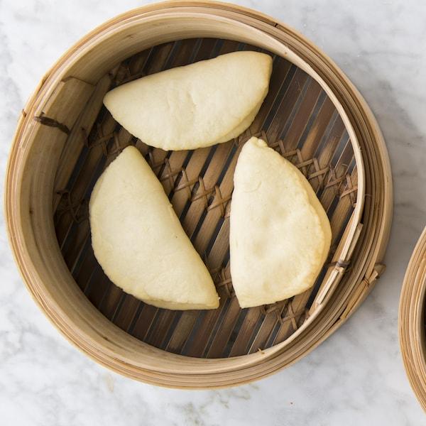 Cinq buns sont dans deux paniers vapeur en bambou.
