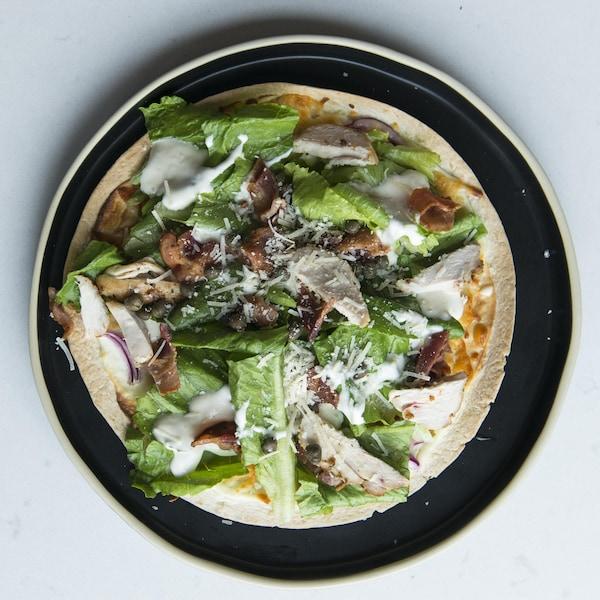 Une salade césar au poulet sur une croute de pizza.
