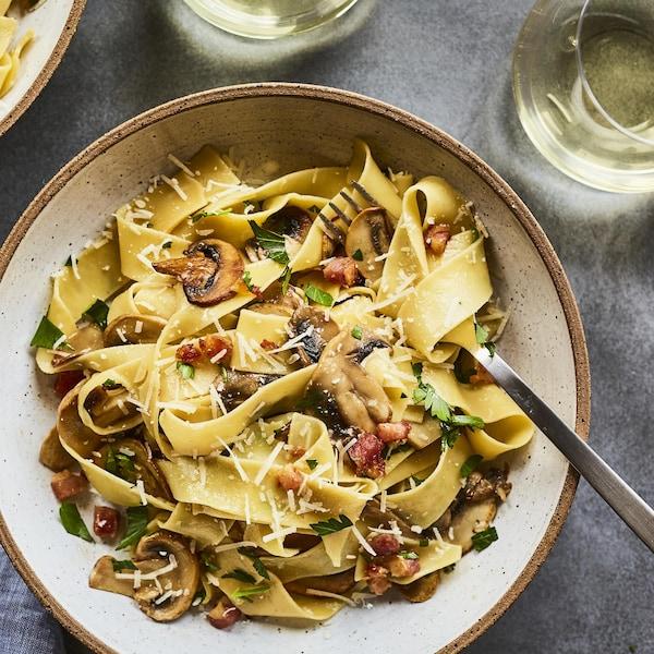 Un plat de pappardelles aux champignons et à la pancetta sur la table.