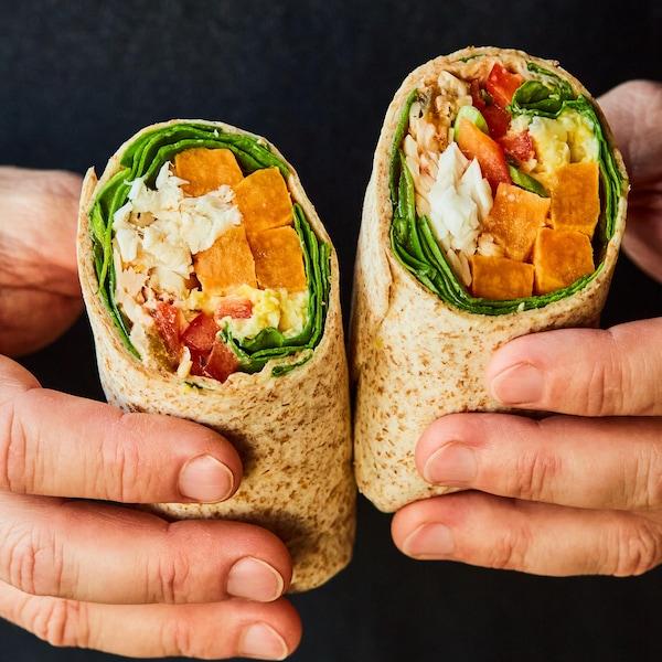 Un homme tient un burrito coupé en deux dans ses mains.