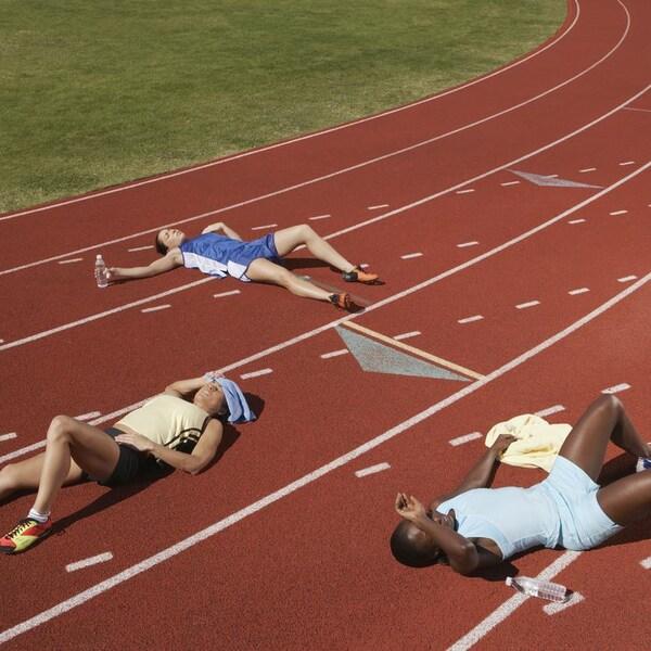 Trois personnes exténuées sur une pistes de course.