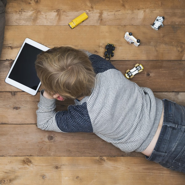 Une mère et son fils sont installés sur le plancher avec une collation, un ordinateur et une tablette.