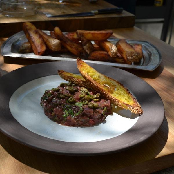 Tartare de cerf à l'huile de colza grillé et frites pont-neuf maison dans une grande assiette.
